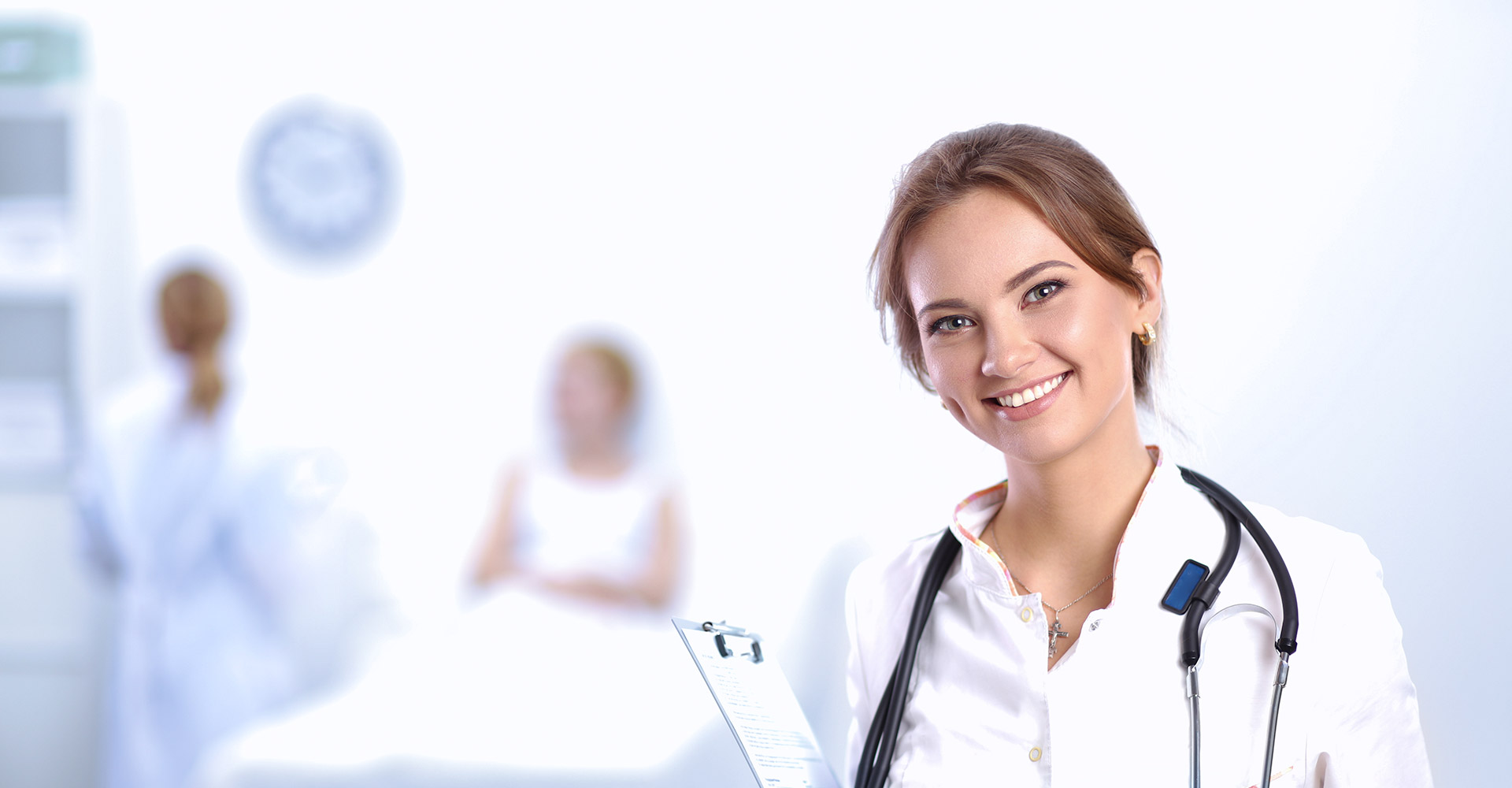 Image of a female doctor smiling at the camera with a clipboard in hand